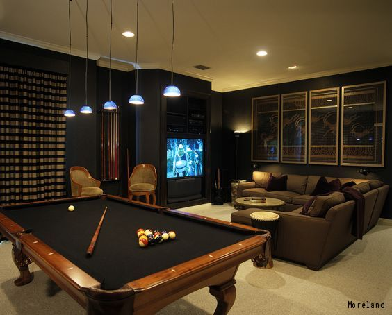 A entertainment den for men with a pool table and seating infront TV