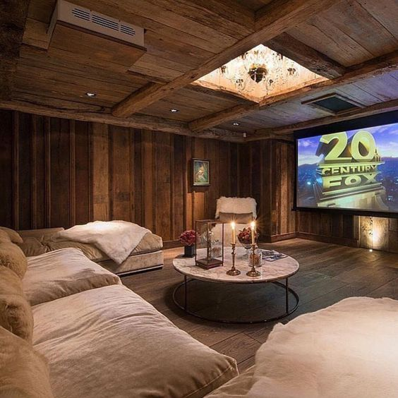 A rustic looking room with natural lighting and sofa infornt of TV